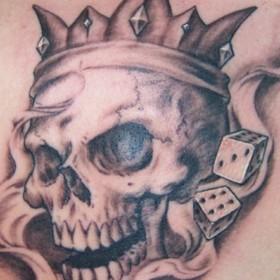 Татуировка корона на черепе с игральными костями на груди у мужчины