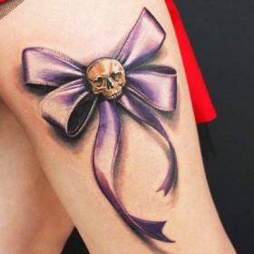 Татуировка на бедрах девушки - бантик с черепом