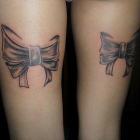 Татуировка на бедре у девушки - бантики