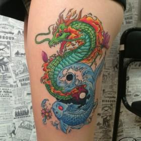 Татуировка на бедре у девушки - дракон и карп