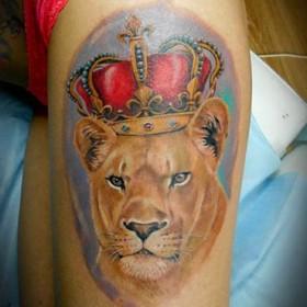 Татуировка на бедре у девушки - лев с короной