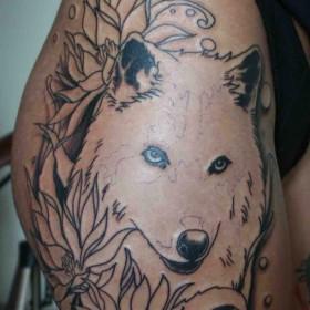 Татуировка на бедре у девушки - волк и цветы