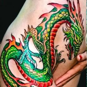 Татуировка на боку у девушки - дракон