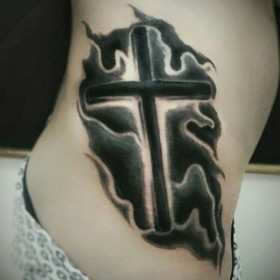 Татуировка на боку у девушки - крест