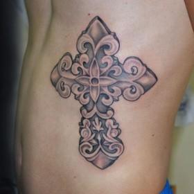 Татуировка на боку у парня - крест