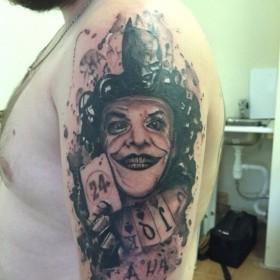 Татуировка на плече у парня - Джокер и Бэтмен