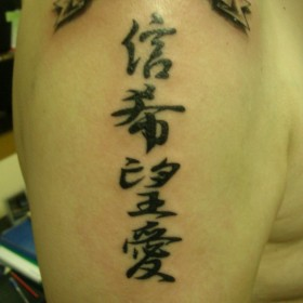 Татуировка на плече у парня - иероглифы