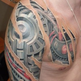 Татуировка на плече у парня в стиле биомеханика