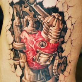 Татуировка на ребрах парня - биомеханическое сердце