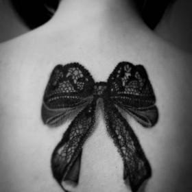 Татуировка на спине у девушки - бантик