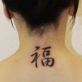 Татуировка на спине у девушки - иероглиф