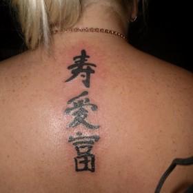 Татуировка на спине у девушки - иероглифы