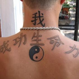 Татуировка на спине у парня - иероглифы и Инь-Янь