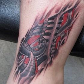 Татуировка на щиколотке парня в стиле биомеханика