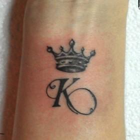 Татуировка на запястье у девушки - корона К