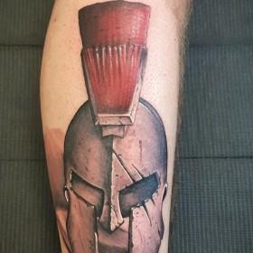 Татуировка шлема гладиатора на голени мужчины