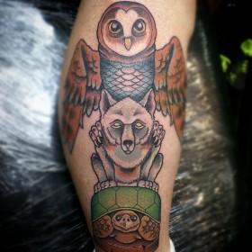 Татуировка тотема совы волка и черепахи на голени парня