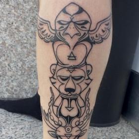 Татуировка тотема животных на голени парня