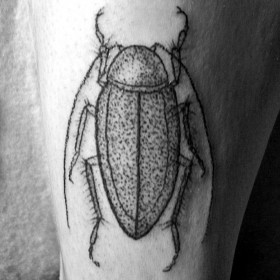 Жук- татуировка черной тушью на ноге парня
