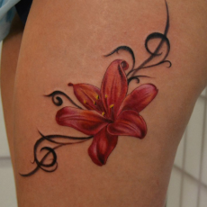 Татуировка на бедре девушки - лилия