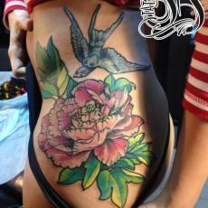 Татуировка на боку у девушки - цветок и ласточка