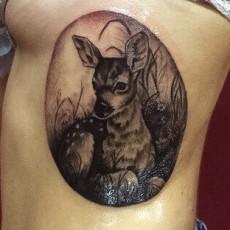 Татуировка на боку у девушки - олень