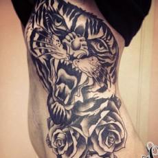 Татуировка на боку у девушки - тигр и розы