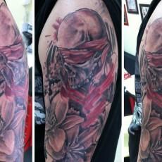 Татуировка на плече у парня - череп и лилии