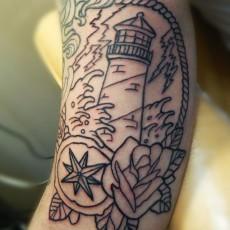 Татуировка на плече у парня - маяк