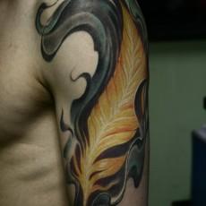 Татуировка на плече у парня - перо