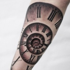 Татуировка на предплечье девушки - спиральные часы