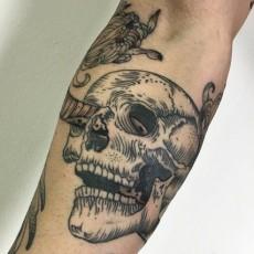 Татуировка на предплечье парня - череп со змеей