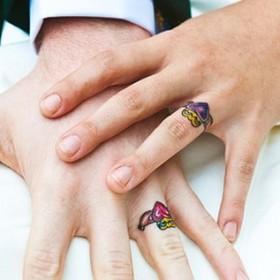 Цветная татуха обручальных колец на пальцах парня и девушки