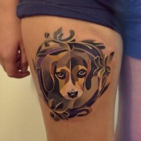 Цветная татушка на бедрах у девушки - собака