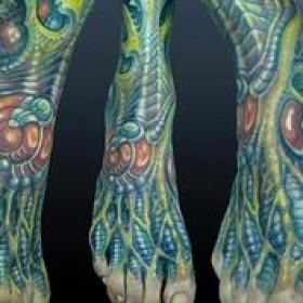 Фото цветного тату в стиле органика на ступне парня