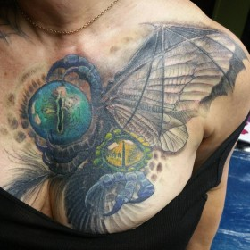 Фото цветной татуировки в готическом стиле на груди девушки