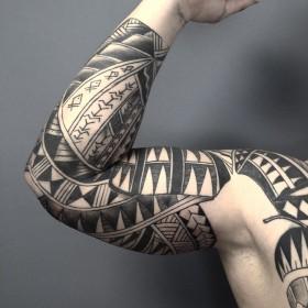 Фото крутой татуировки в самоанском стиле на рукаве мужчины