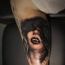 Фото крутой татуировки вампирши в готическом стиле на бицепсе парня