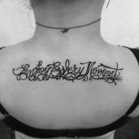 Фото тату в стиле надписи на спине девушки