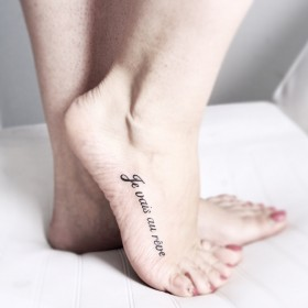 Фото тату в стиле надписи на ступне девушки