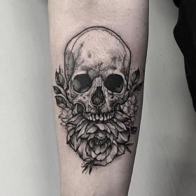 Фото татуировки черепа в готическом стиле на предплечье девушки