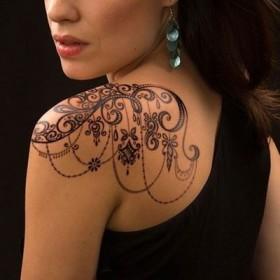 Фото татуировки узора в готическом стиле на плече девушки