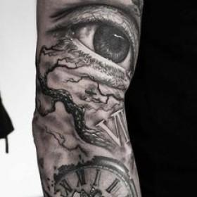 Фото татуировки в стиле сюрреализм на рукаве парня