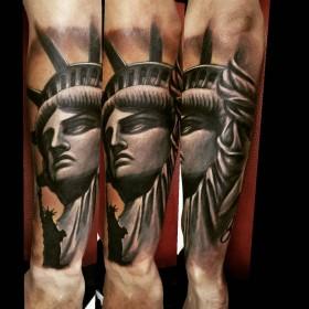 Изображение статуи свободы на предплечье мужчины
