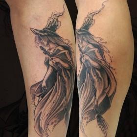 Изображение ведьмы с метлой на голени девушки