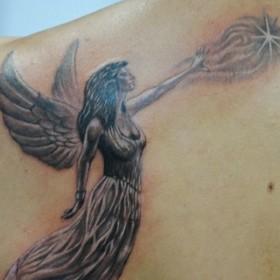 Красивая тату на лопатке у девушки - ангел в виде девушки и звезда