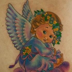 Красивая тату на лопатке у девушки - ангел в виде ребенка
