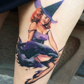 Крутое изображение ведьмы на метле на бедре девушки