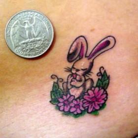 Маленькая тату на животе девушки - заяц с цветами