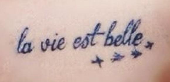 Надпись на французском - татуировка на ключице девушки